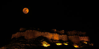 "Red Moon over Jaisalmer Fort in India. Jaisalmer Fort in the Deserts of Rajasthan in India is rightly called ""The golden Fort"". The Full moon over the Fort Royalty Free Stock Image"