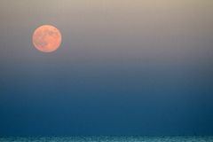 Red Moon that rises above the blue sea Royalty Free Stock Images