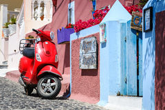 Red moor scooter as a part of decoration at color street of Thira town Stock Photos