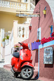 Red moor scooter as a part of decoration at color street of Thira town Royalty Free Stock Photography