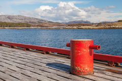 Red mooring bollard on wooden pier Royalty Free Stock Images