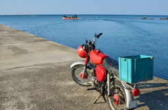 Red moped. Standing on concrete jetty near blue sea waters Royalty Free Stock Photos