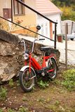 Red moped. On the street leaning against a wall stock images