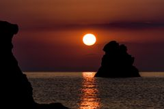 Warm sunrise over sea rocks in Taormina, Sicily stock image