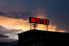 Red Motel Sign with Brilliant Sunset. Illuminated red motel sign and motel silhouette, with a brilliant sunset in the background Royalty Free Stock Image
