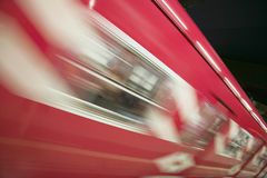 Red motion blur of speeding train at Metro subway train station in Madrid, Spain Stock Image