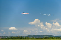 Red motor airplane tows glider up in the air Royalty Free Stock Photo