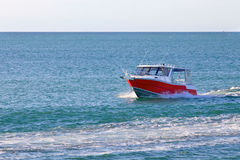 Red motor boat floating in the ocean or sea Stock Photo