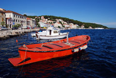 Red motor boat in Mali Losinj harbour,Croatia. Red motor boat and houses in Mali Losinj port,Croatia Stock Photo