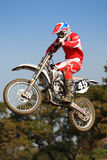 Red Motor Cross Jump. A motor cross racer in a distinctive red suit jumps from a hill Stock Image