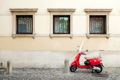 Red motorbike. Red stylish motorbike parked at the street of ancient town in front of old classic building's wall Stock Photo