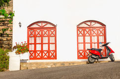 Red motorbike in front of typical Greek house Stock Photography