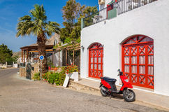 Red motorbike in front of typical Greek house Royalty Free Stock Image