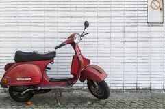 Red motorbike in front of a white wall royalty free stock photos