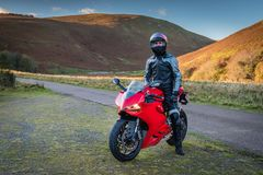 Red Motorbike with Rider. In Upper Coquetdale, Northumberland on a sunny day Stock Image