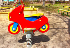 Red motorcycle, children`s playground in the spring Stock Photography