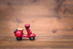 Red motorcycle vespa on old and vintage rustic wooden background. Using for Christmas greeting card, New Year and happy birthday present decoration concept Royalty Free Stock Photos