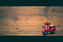 Red motorcycle vespa on old and vintage rustic wooden background. Using for Christmas greeting card, New Year and happy birthday present decoration concept Stock Photos