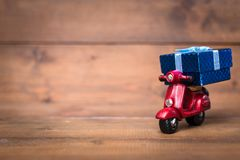 Red motorcycle vespa are Transporting Blue gift box on old and v. Intage rustic wooden background. using for Christmas greeting card, New Year and happy birthday Stock Images