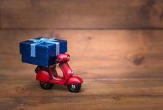 Red motorcycle vespa are Transporting Blue gift box Stock Photos