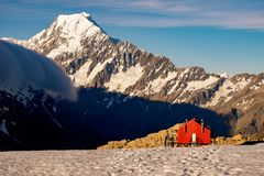 Red mountain hut and Mt Cook in the background, New Zealand Stock Photo