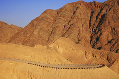 The red mountains of the Arava desert in the setting sun. Mountain Solomon and mountain road. Royalty Free Stock Photo