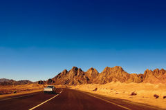 Red mountains of Ras Mohammed National Park. Open road and car moving towards the red mountains of Ras Mohammed National Park on the Sinai peninsula in Egypt Stock Photography