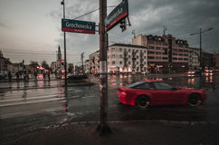 Red moving car on a crossroad. A crossroad in Warsaw with moving vehicles after heavy rain stock image