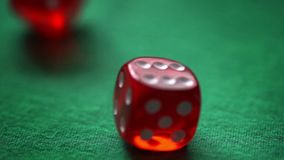 Red moving casino dices on green background stock footage