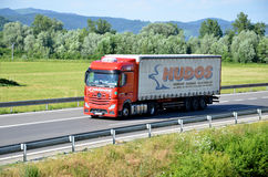 Red moving Mercedes-Benz Actros truck coupled with semi-trailer located on slovak D1 highway surrounded by green field and trees. Stock Photography