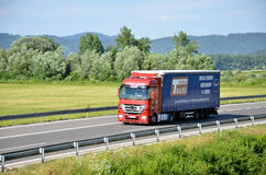 Red moving Mercedes-Benz Actros truck coupled with semi-trailer located on slovak D1 highway surrounded by green field and trees. Royalty Free Stock Images