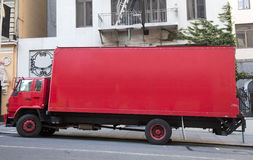 Red Moving Van. Side view of parked red moving van  truck on city street Stock Photo