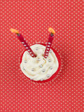 Red muffin candles. Red muffin on red background with white polka dots with two candles seen from above Stock Image