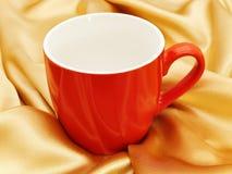 Red mug. Photo of single red mug at the golden fabric drapery Stock Image