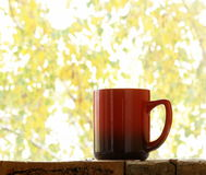 Red mug on the background of autumn window Royalty Free Stock Photos