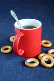 Red mug of black tea and dryings are on the table close-up Stock Photos