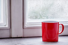 Red mug on bright morning window sill Royalty Free Stock Photography
