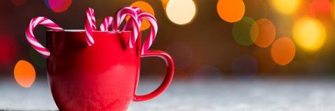 Red mug with candy canes, with christmas lights bokeh. Festive Christmas web banner stock photos