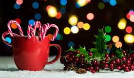 Red mug with candy canes in snow with defocussed fairy lights, bokeh royalty free stock photos