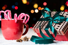 Red mug with candy canes in snow with nicely wrapped present Stock Photos