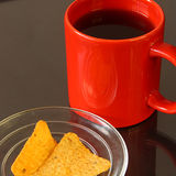 Red mug and chips. Red mug and yellow chips on glass plate Stock Photography