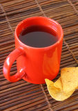 Red mug and chips on glass plate Stock Photo