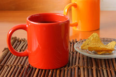 Red mug and chips on glass plate Stock Photography