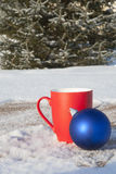 Red mug with Christmas balls in the winter forest Royalty Free Stock Image