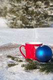 Red mug with Christmas balls in the winter forest Royalty Free Stock Photography