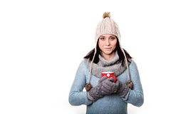 Red mug with coffee in the hands of the girl in a knitted hat is Royalty Free Stock Photo