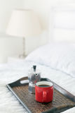 Red mug of coffee with steel coffee percolator on bed Stock Photos