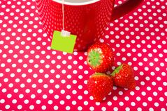 Red mug cup with teabag and strawberries over red background like fruit tea concept. P with teabag and strawberries over red background like fruit tea concept royalty free stock image