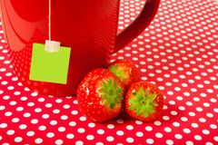 Red mug cup with teabag and strawberries over red background like fruit tea concept. P with teabag and strawberries over red background like fruit tea concept royalty free stock photography