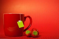 Red mug cup with teabag and strawberries over red background like fruit tea concept. P with teabag and strawberries over red background like fruit tea concept royalty free stock photo